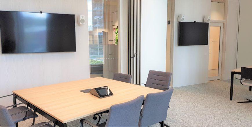 Neuvottelutila Retoriikan ensimmäisessä kerroksessa, josssa tuoleja ja pöytiä aseteltu esimerkiksi ryhmätöitä varten, kaksi näyttöä seinillä.