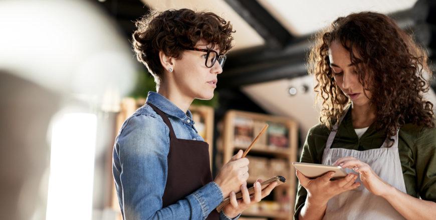 Kaksi yrittäjää suunnittelee apunaan muistiinpanovälineet ja tabletti.
