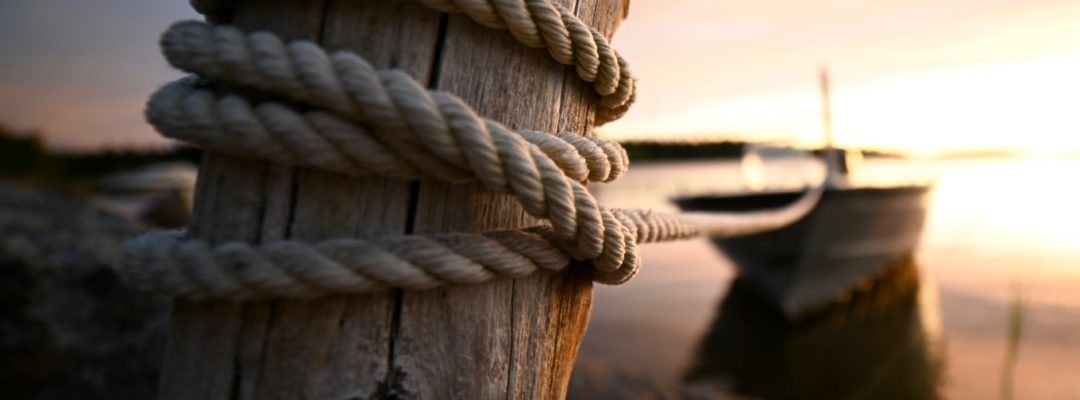 Boat tied witha rope to a wooden pole.
