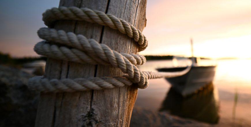Båt fast i en stolpe med ett rep.