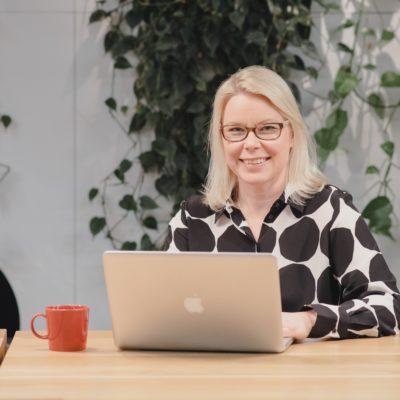 Företagaren Tuuli ilves sitter framför datorn och ler mot kameran.