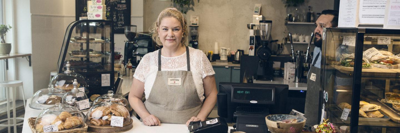 Nainen seisoo kahvilassa tiskin takana.