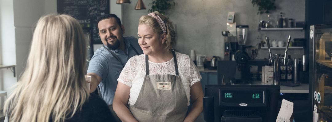 Kahvilatyöntekijät palvelemassa asiakasta