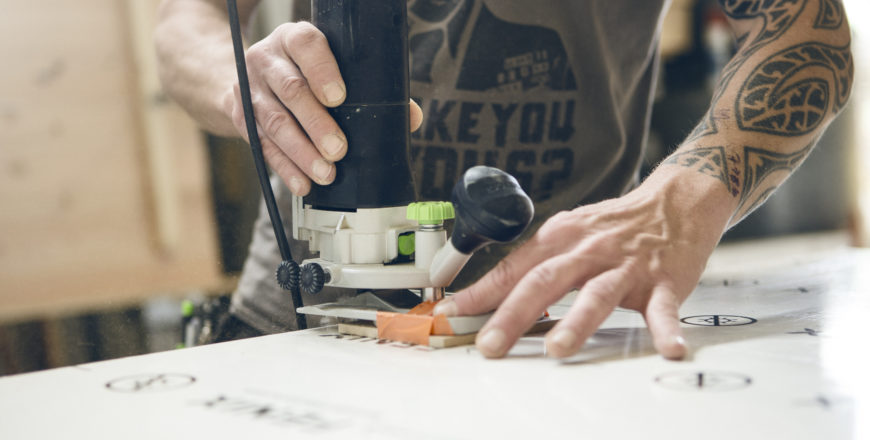 Mies tekee koneella töitä. Toinen käsi on tatuoitu.