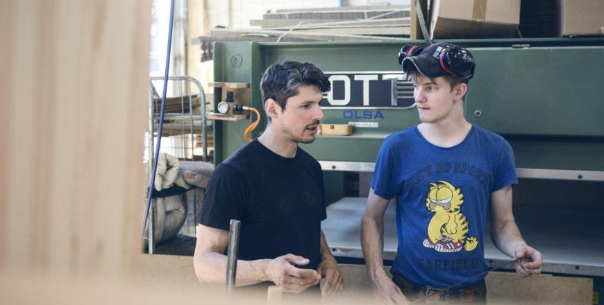 Puuverstaan kaksi työntekijää keskustelevat keskenään.