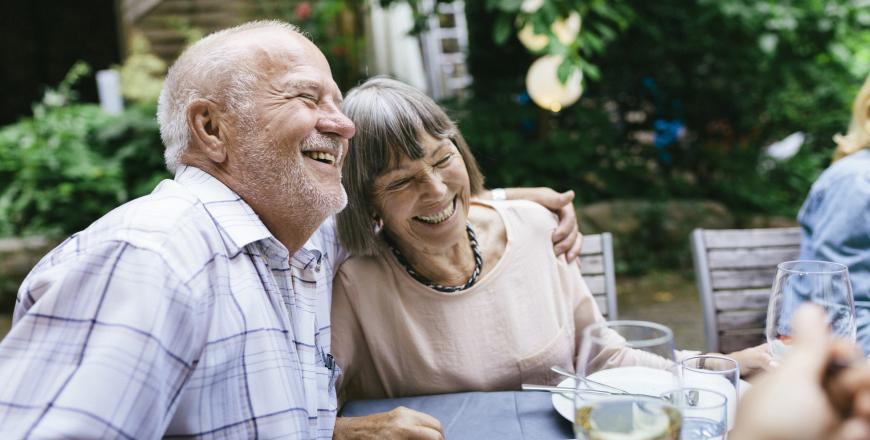Hymyilevä eläkeläispariskunta istuu pöydän ääressä.
