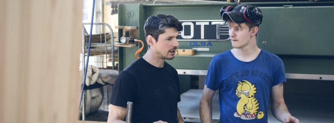 Två personer strå och diskuterar på en arbetsplats.